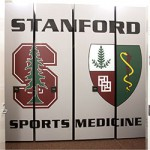 Sports team equipment storage featuring custom end panels with university logo
